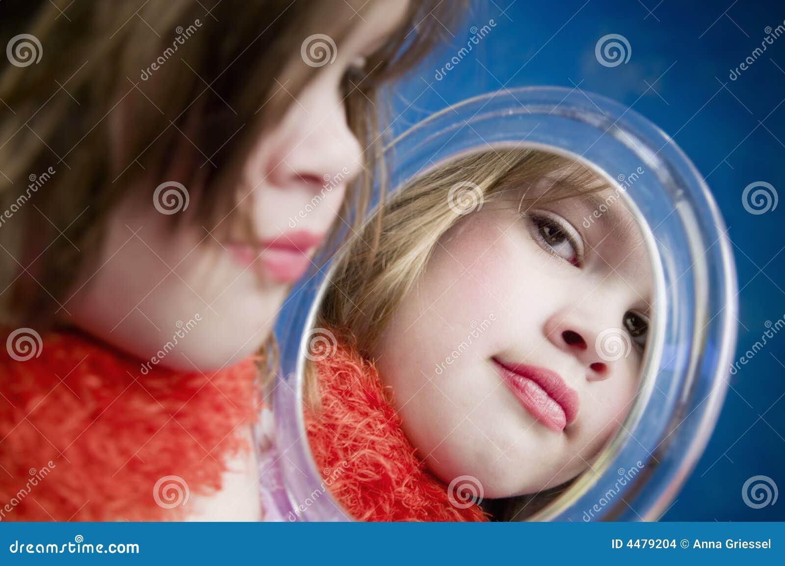 Menina que olha um espelho