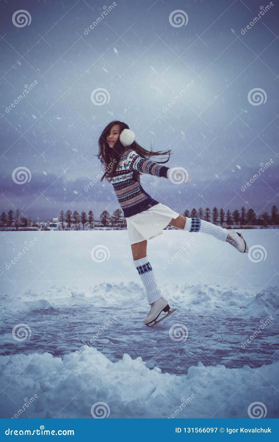 Menina que patina fora no inverno