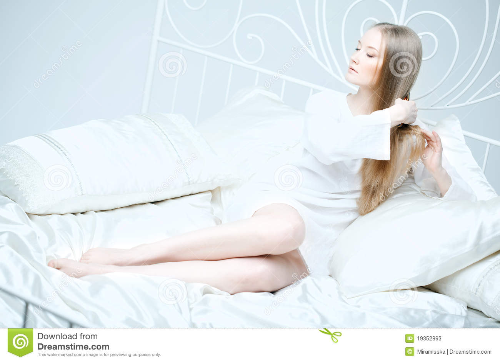 Menina que penteia seu cabelo na cama