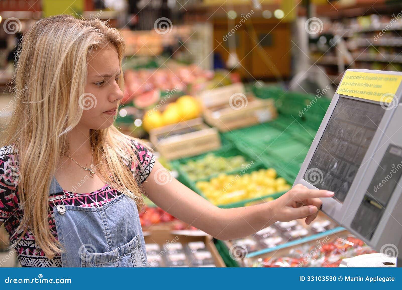 Menina que pesa bens na loja