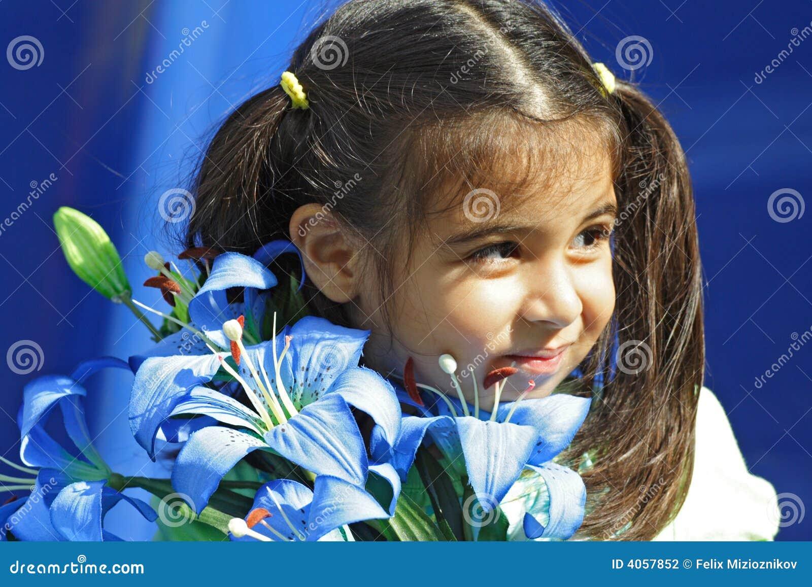 Menina que prende flores azuis