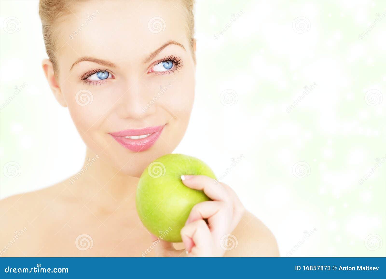 Menina que prende uma maçã verde