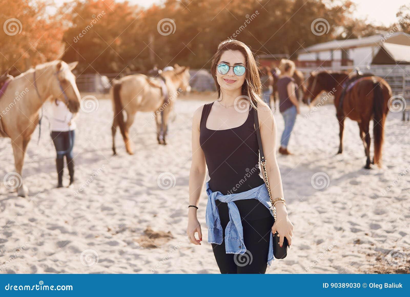 Menina que prepara-se para montar um cavalo