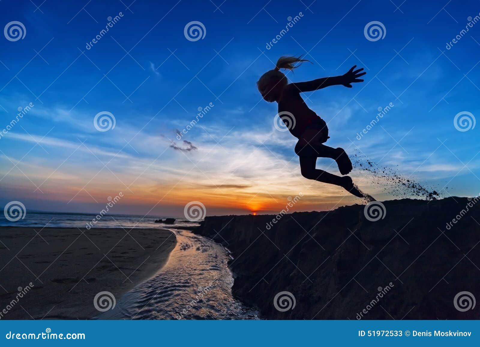 A menina que salta na praia do por do sol
