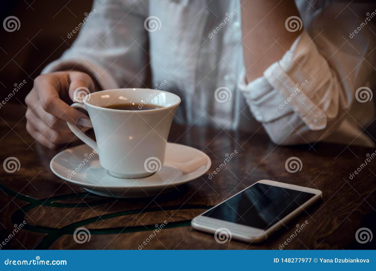 Menina que senta-se em um café em uma camisa branca com uma xícara de café e um telefone