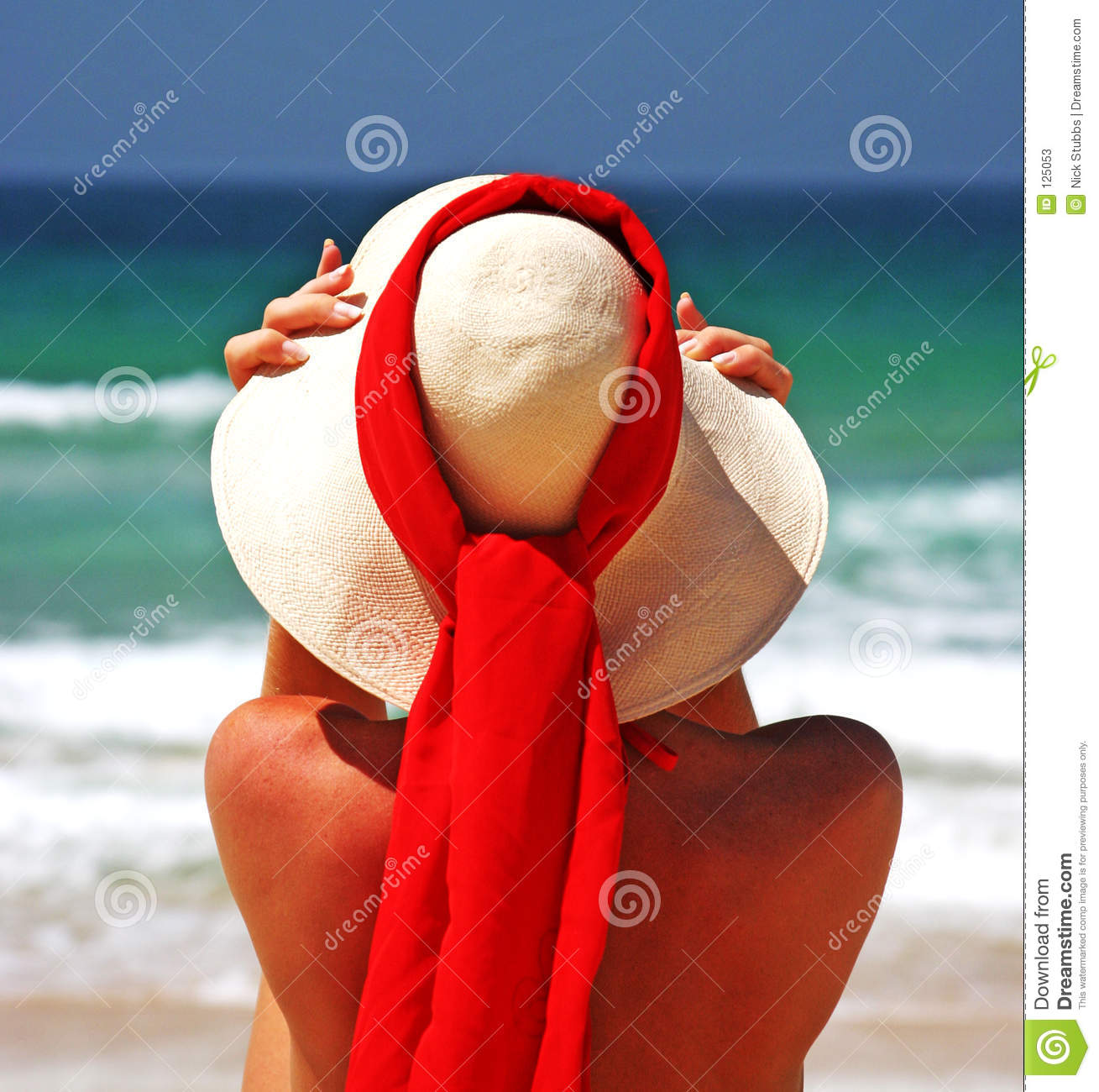 Menina que senta-se na praia arenosa no sol que ajusta o chapéu. Céu azul, lenço azul do vermelho do mar. Spain.