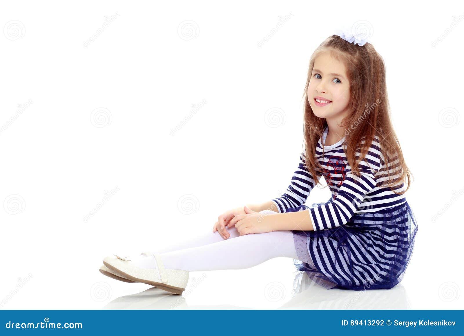 Menina que senta-se no assoalho