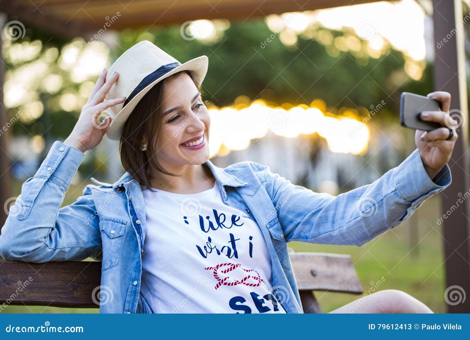 A menina que senta-se no parque e faz o selfie, feliz