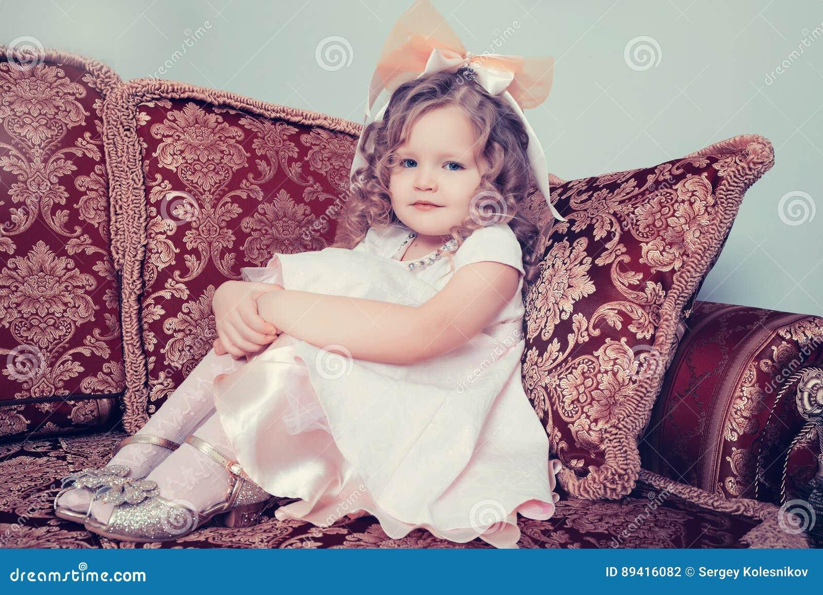 Menina que senta-se no sofá que abraça seus joelhos com suas mãos