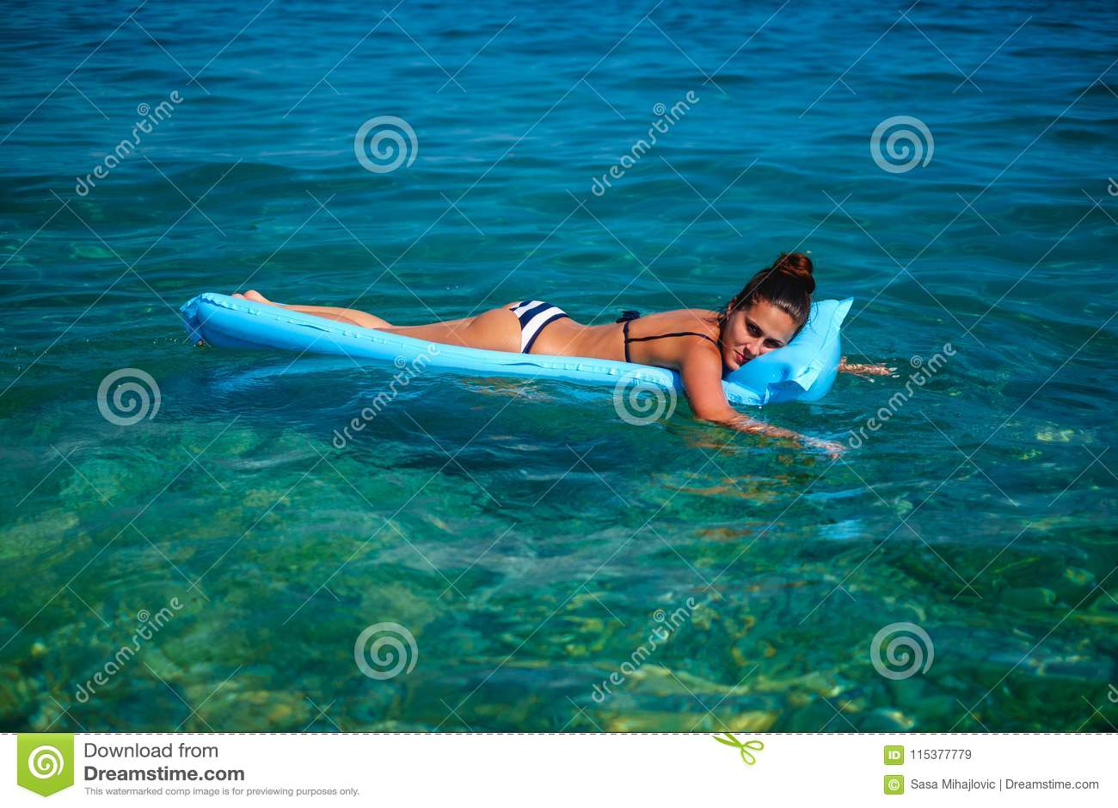 Menina que sorri ao descansar em uma cama de flutuação