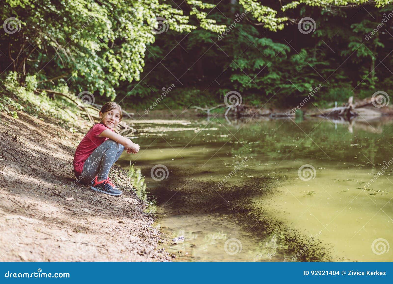 Menina que squatting pelo lago
