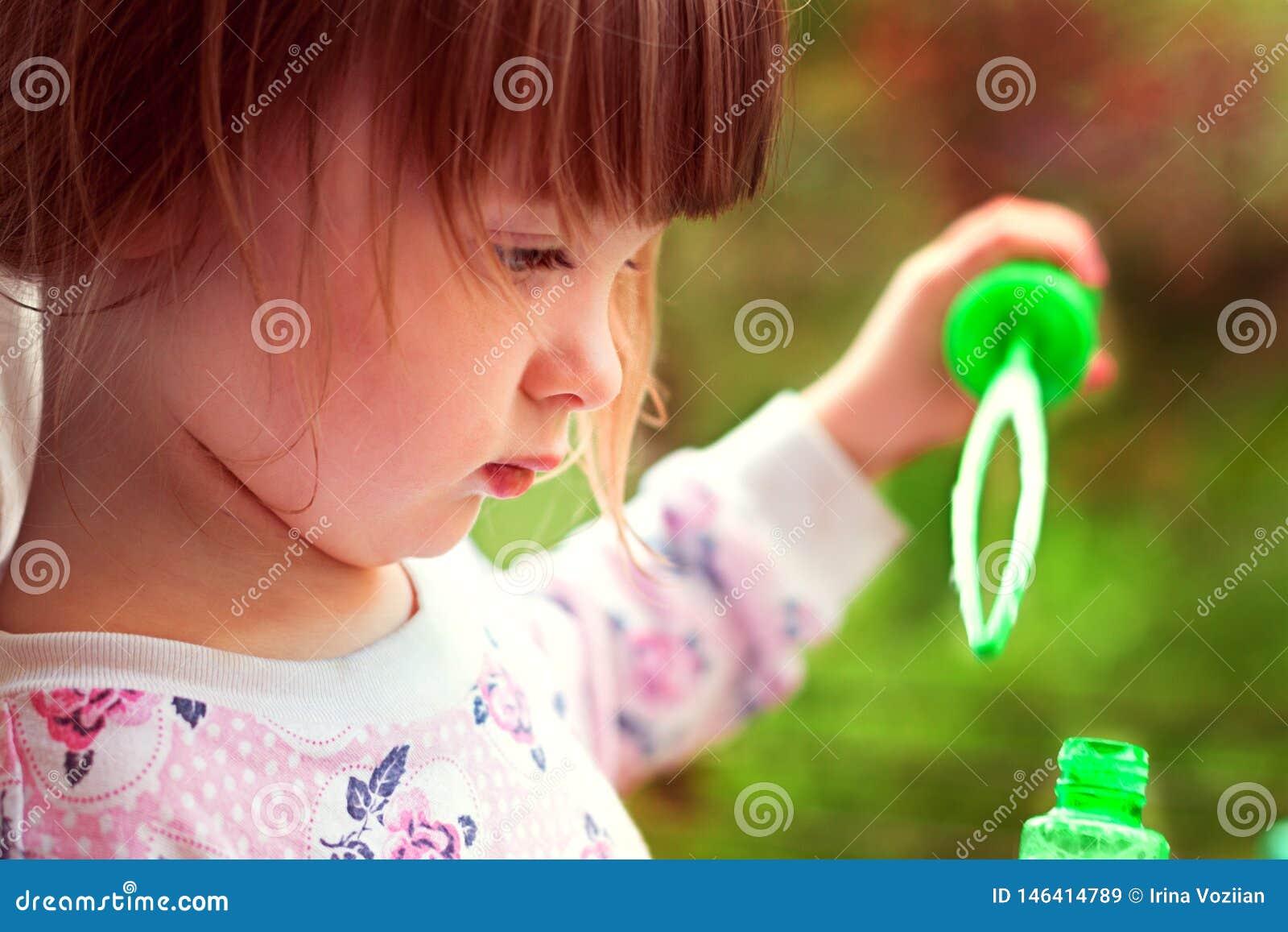 Menina que tenta fundir bolhas de sabão