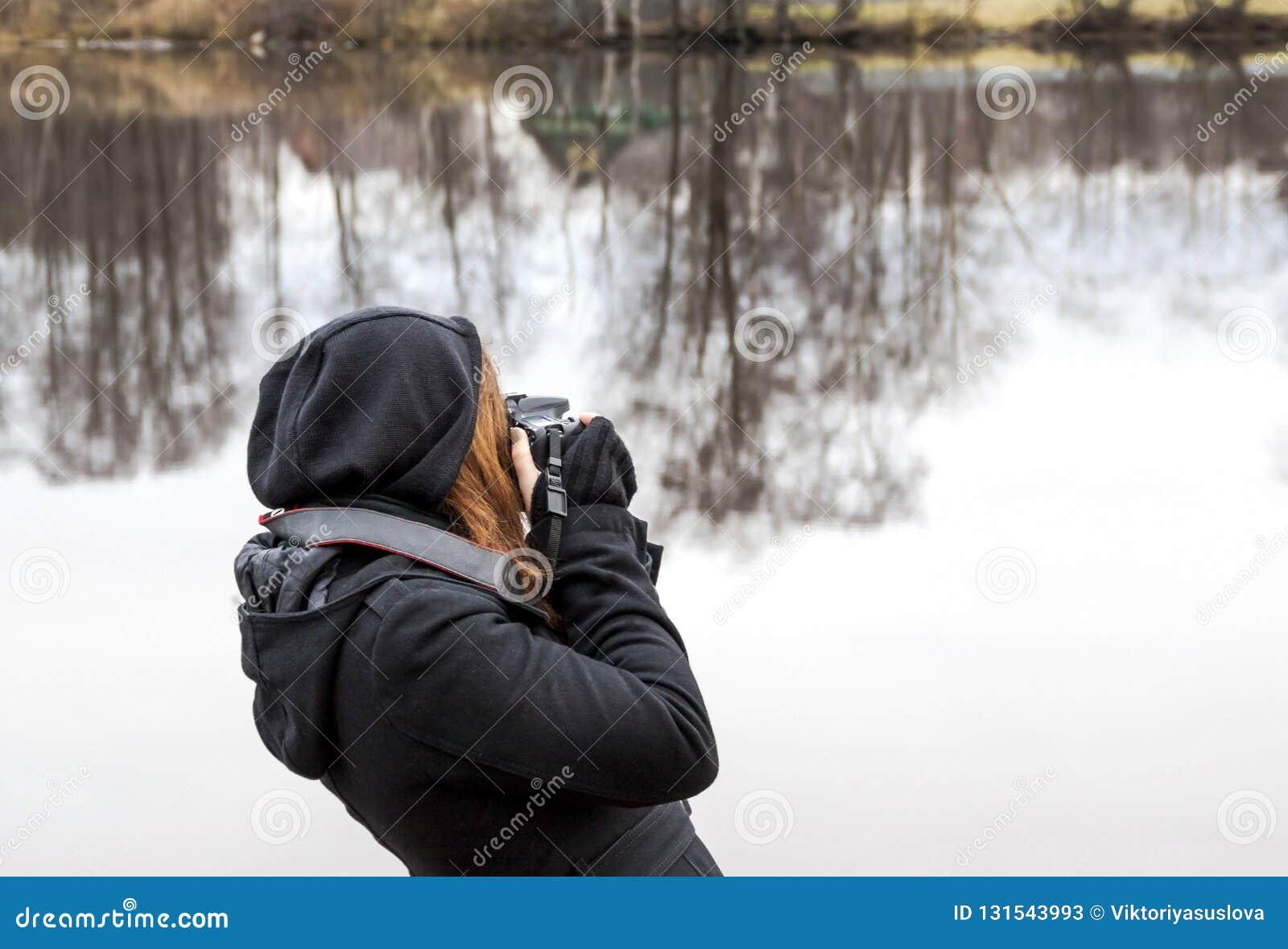 Menina que toma imagens na câmera durante uma viagem ao lago
