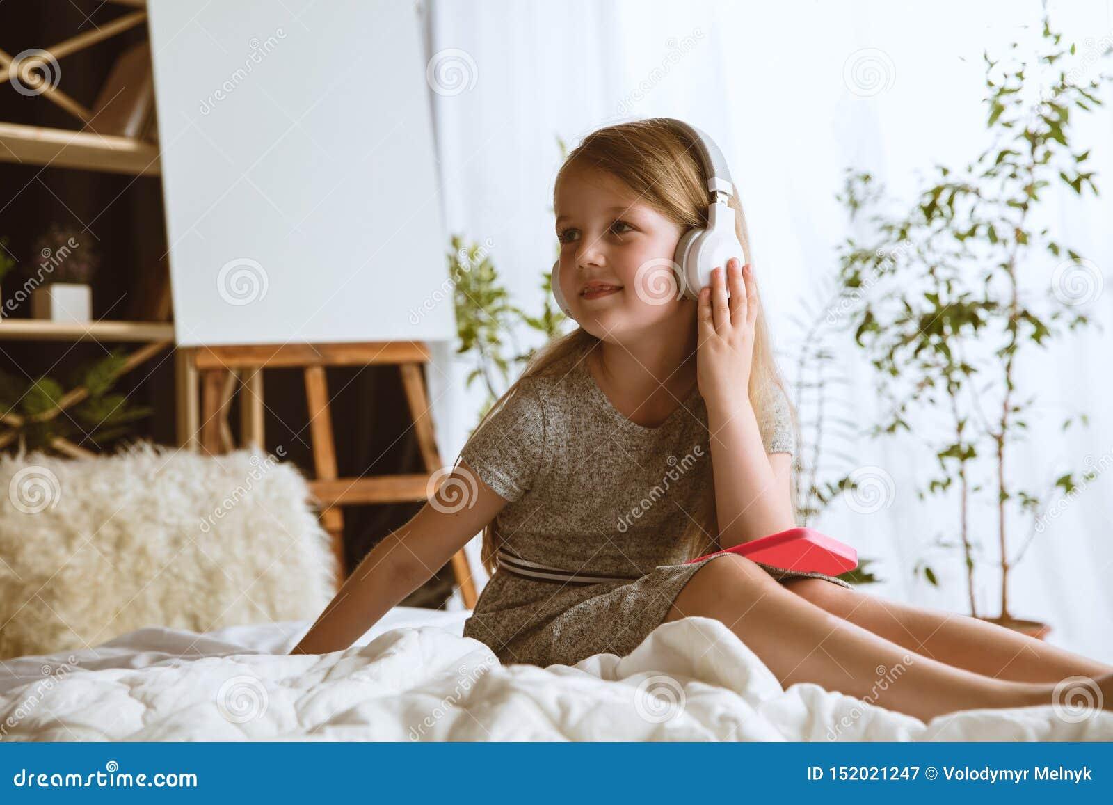 Menina que usa dispositivos diferentes em casa