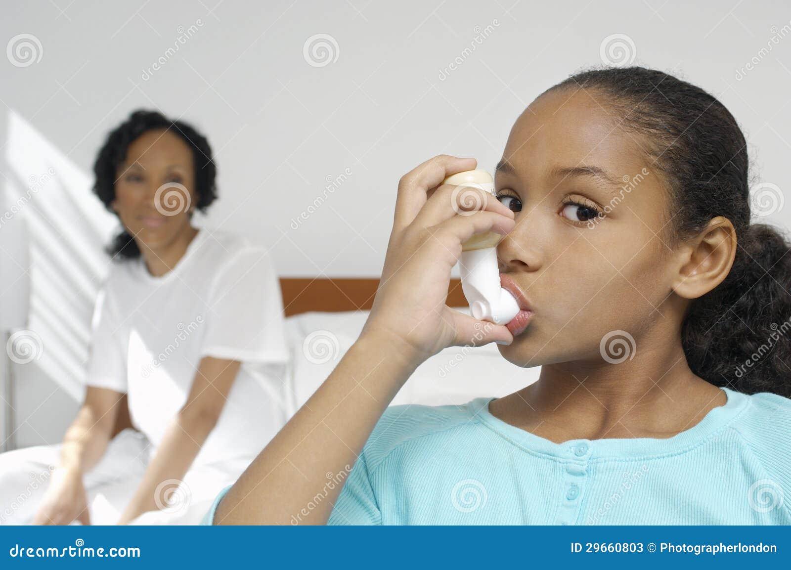 Menina que usa o inalador da asma