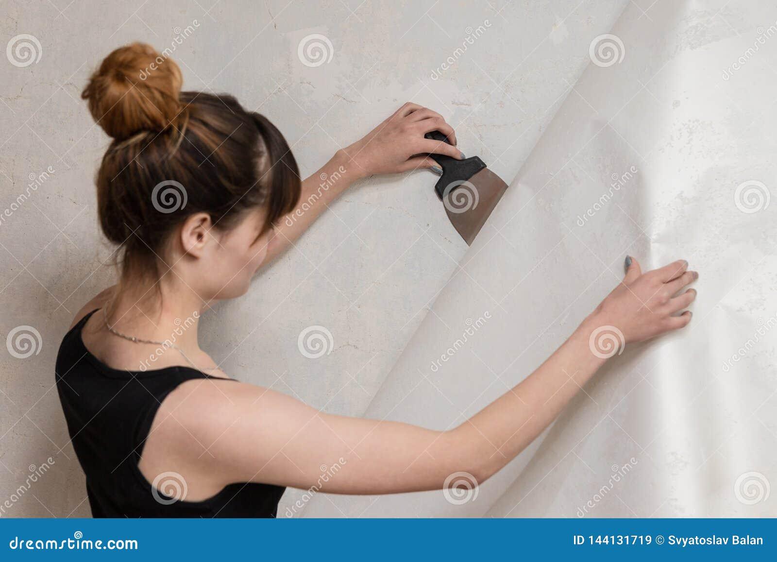 A menina rasga fora o papel de parede velho do muro de cimento e guarda uma espátula