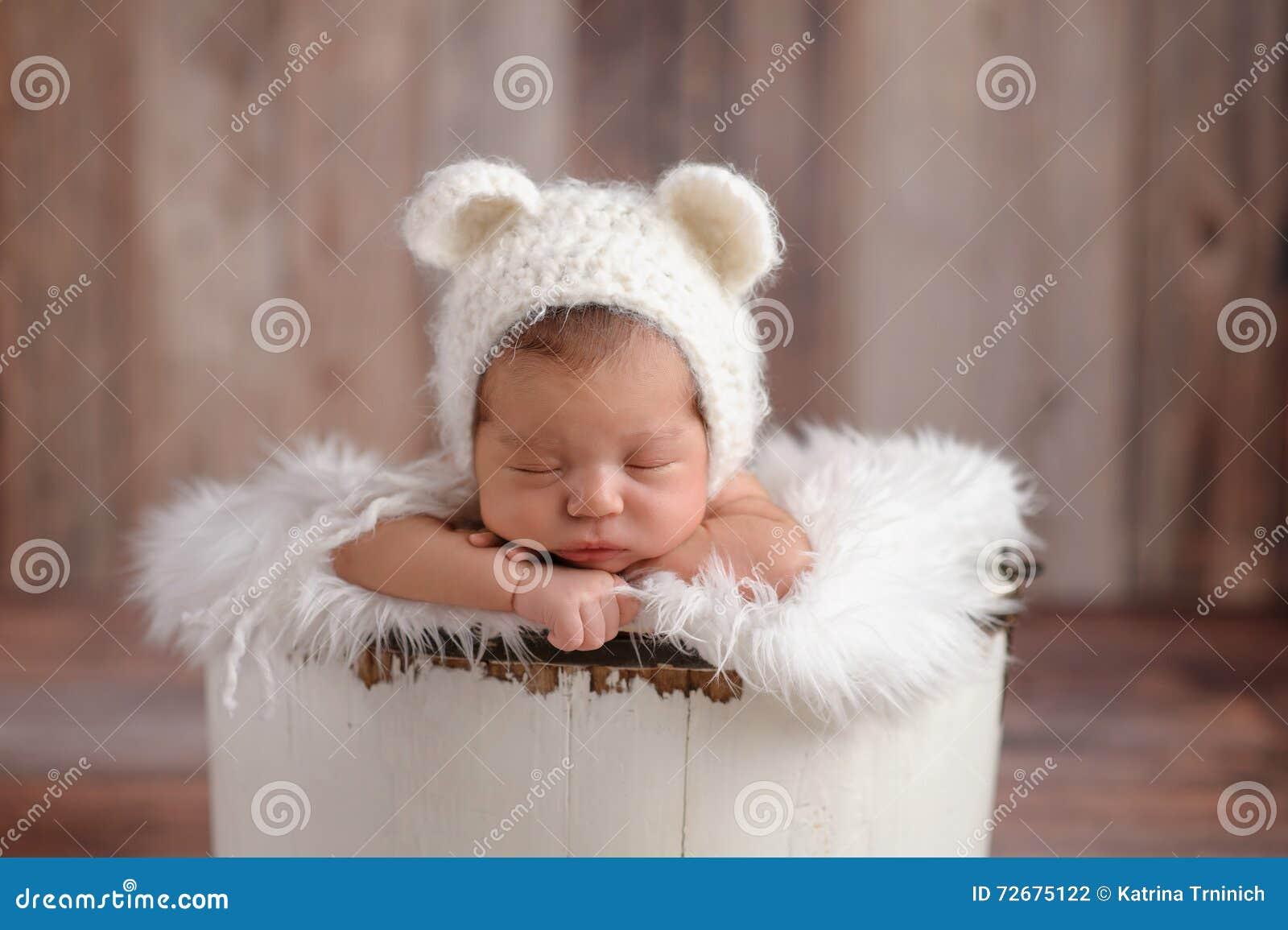 Menina recém-nascida que veste um chapéu do urso branco