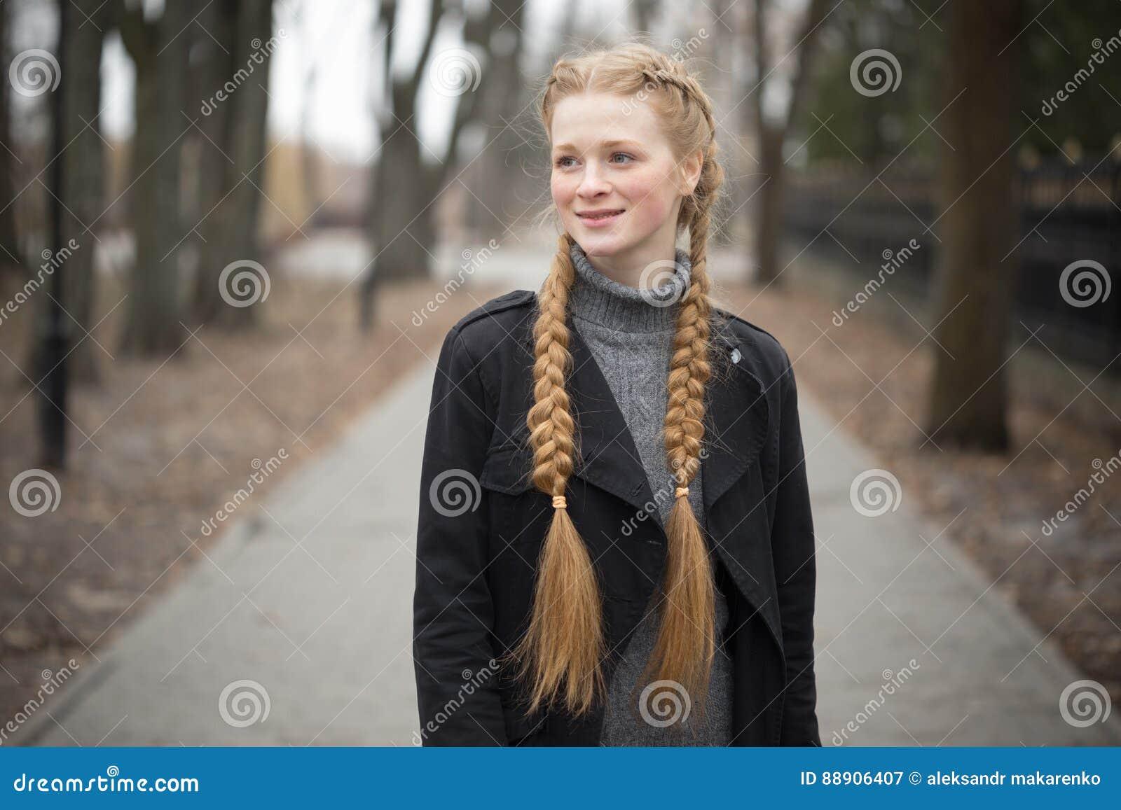 Menina ruivo com mola das tranças na natureza