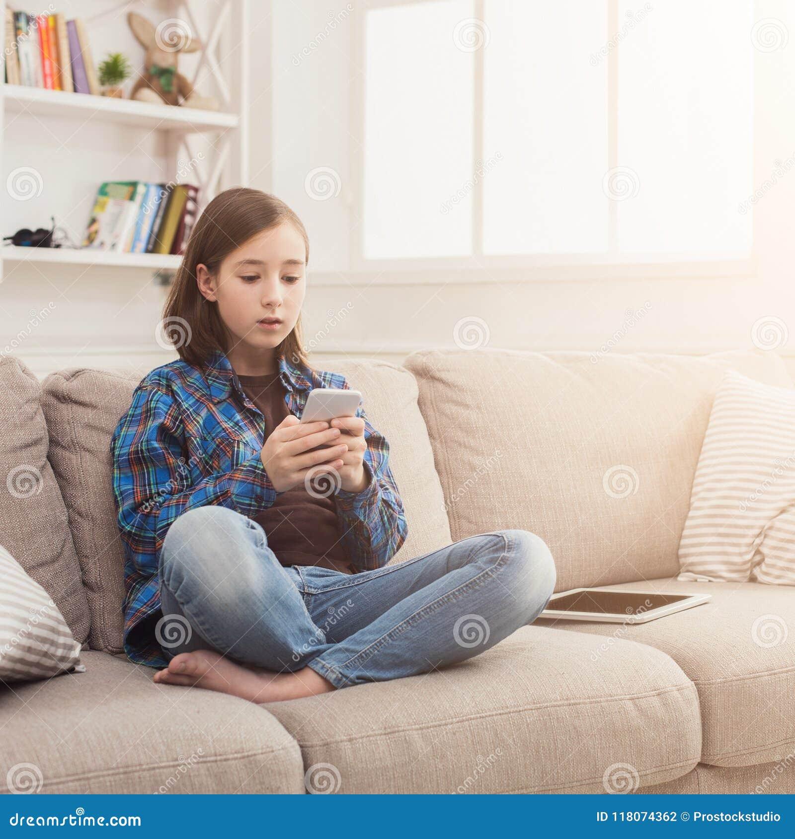 Menina séria com smartphone em casa