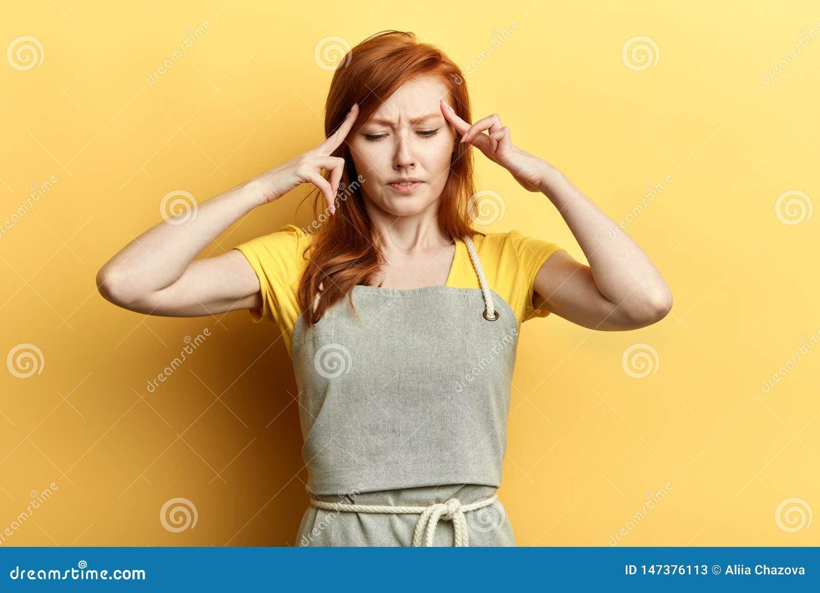 A menina séria confundida pensativa do gengibre mantém os dedos em templos