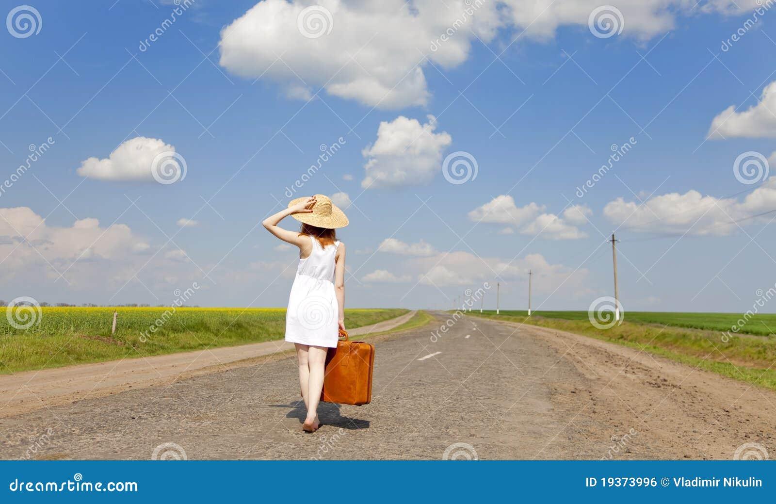 Menina só com a mala de viagem na estrada secundária.