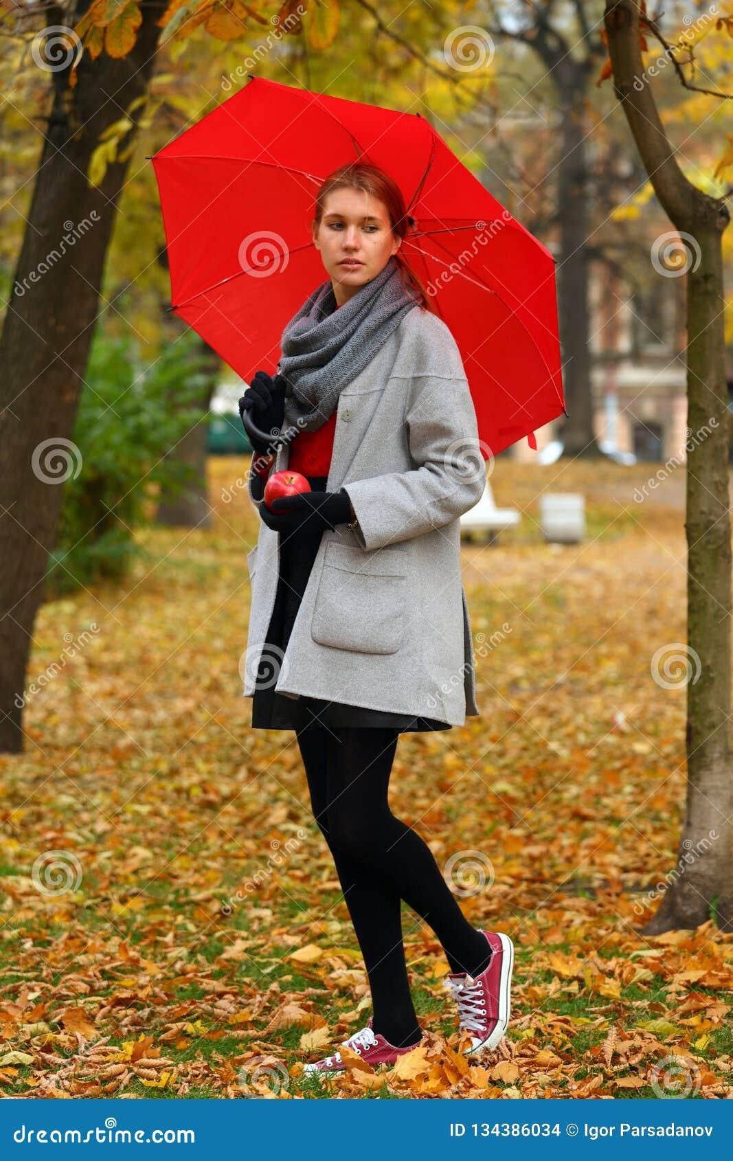 Menina só com o guarda-chuva vermelho no parque do outono