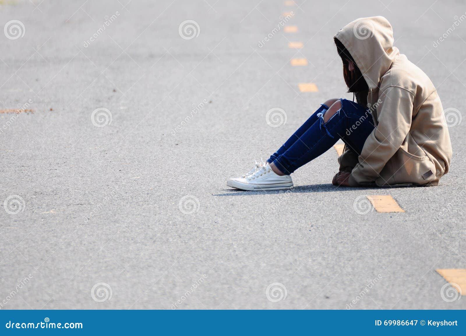 Menina só que senta-se na estrada