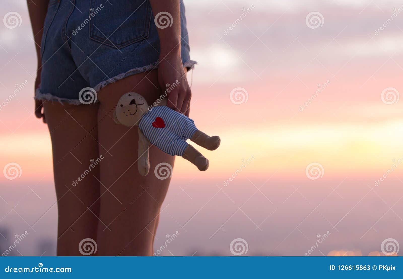 Menina só triste com o urso de peluche no por do sol