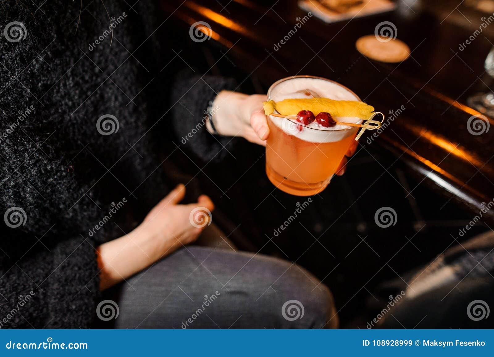 A menina senta-se em um contador da barra e guarda-se um cocktail alaranjado alcoólico na mistura ácida