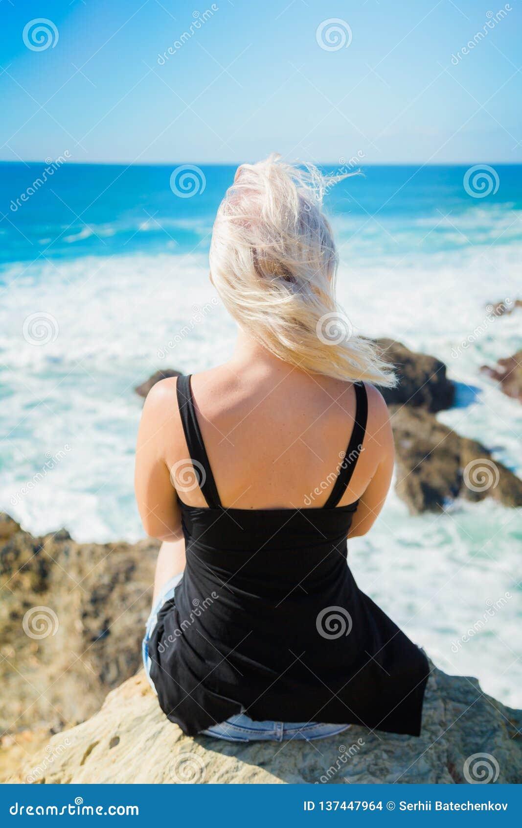 A menina senta-se em um penhasco acima do oceano