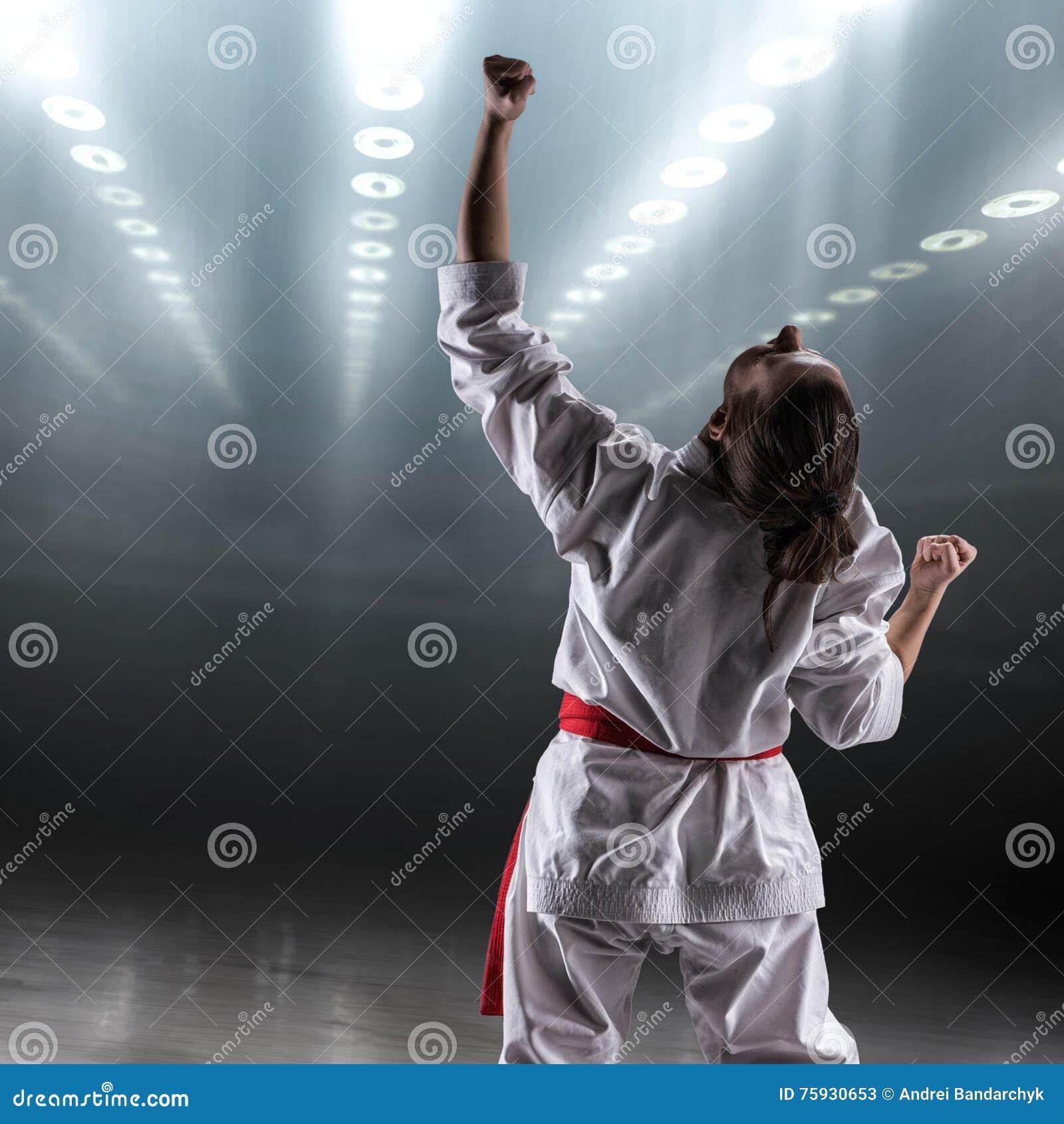 A menina  sexy  em um karaté do quimono exulta a vitória