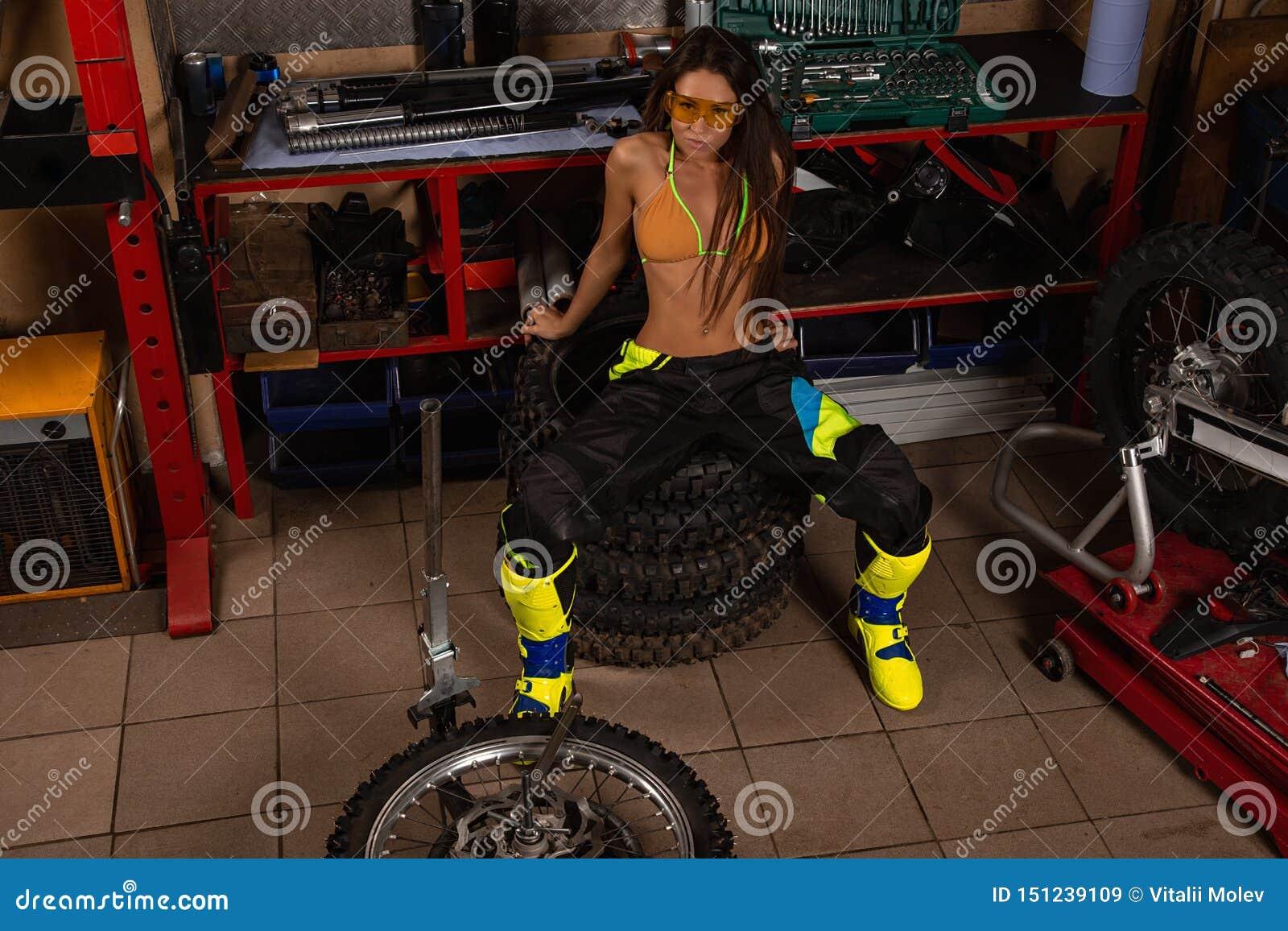 Menina  sexy  na garagem com pneus da bicicleta