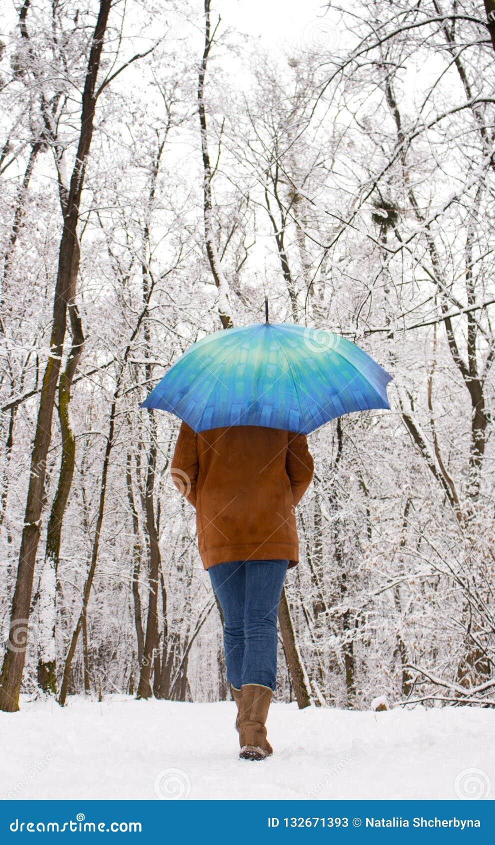 Menina sob o guarda-chuva azul no conceito nevado da queda de neve da floresta Mulher sob a chuva molhada da neve no parque do in
