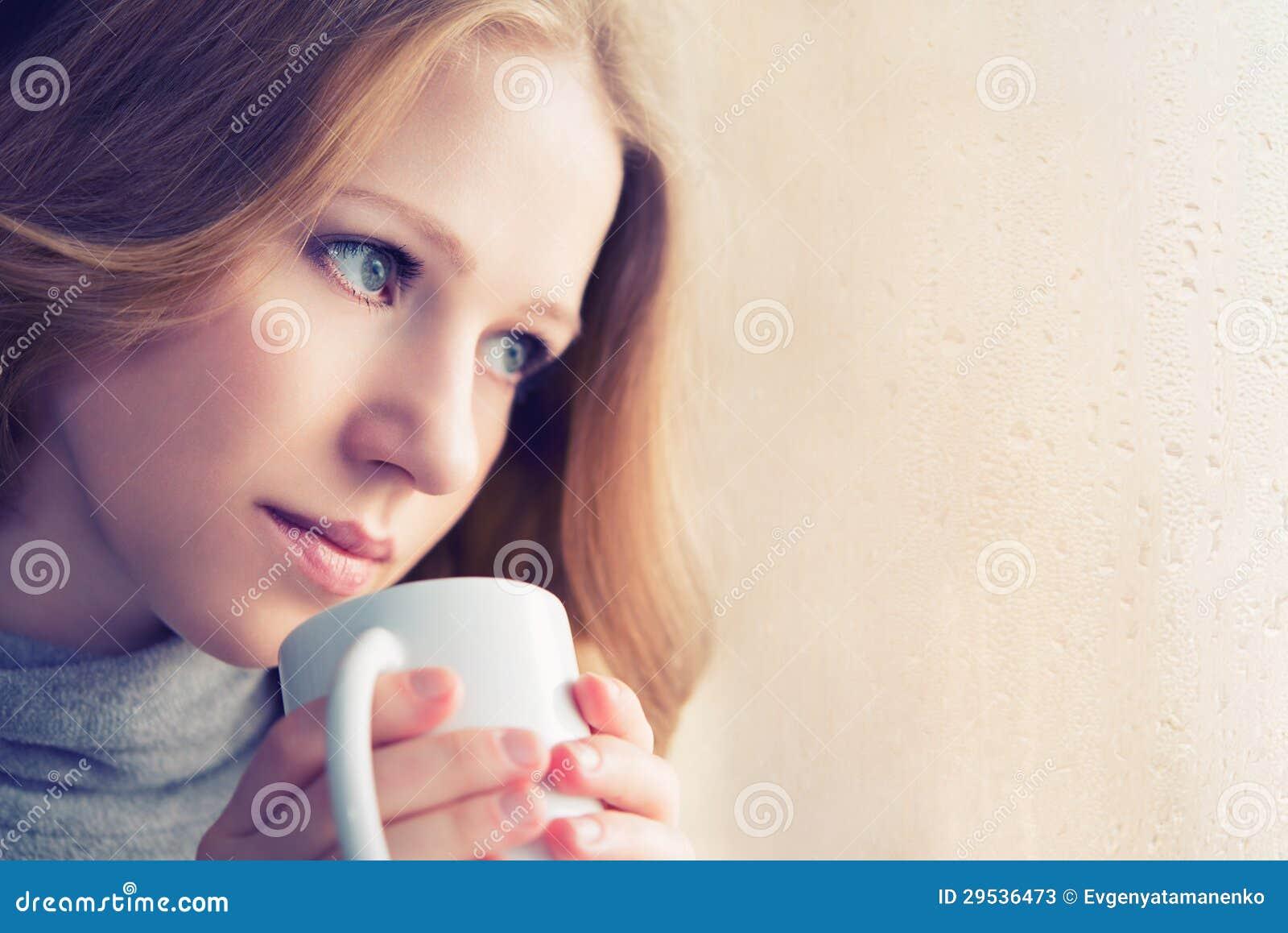 Menina sonhadora bonita com um copo do café quente no indicador