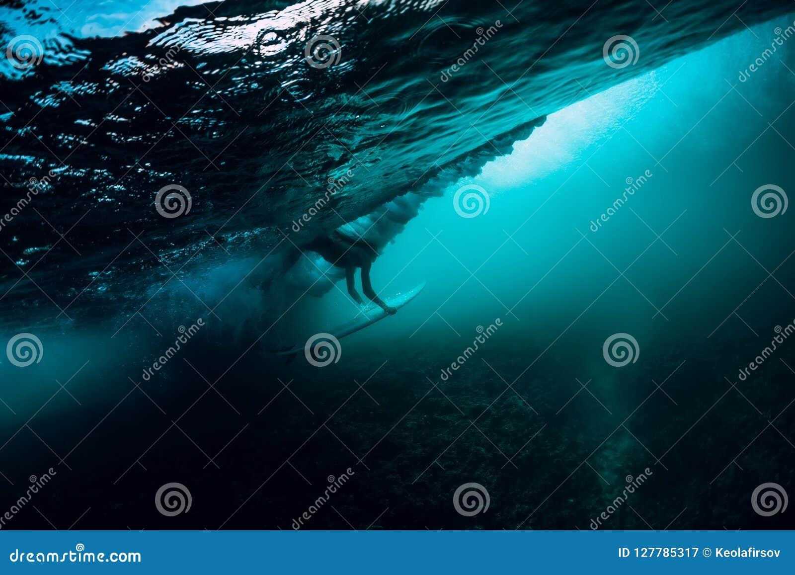 A menina sozinha do surfista com prancha faz o mergulho do pato subaquático com a onda de oceano grande