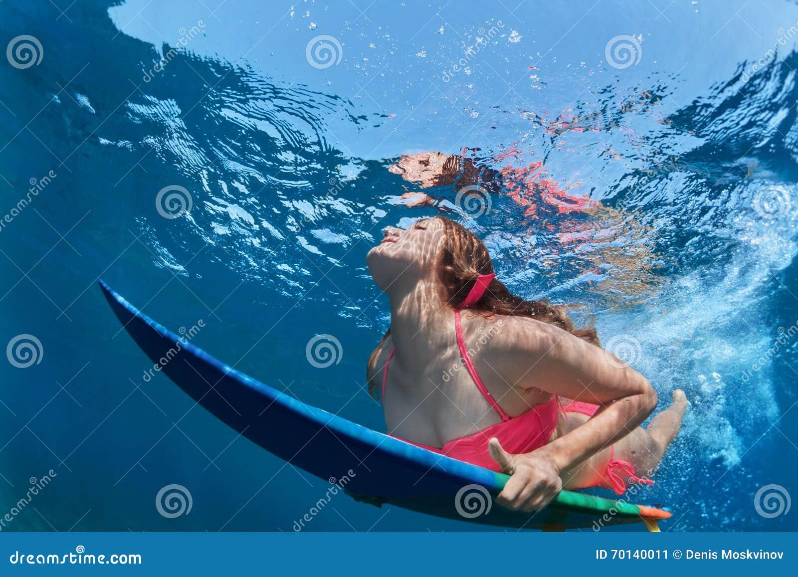 A menina surfando com placa mergulha sob a onda de oceano