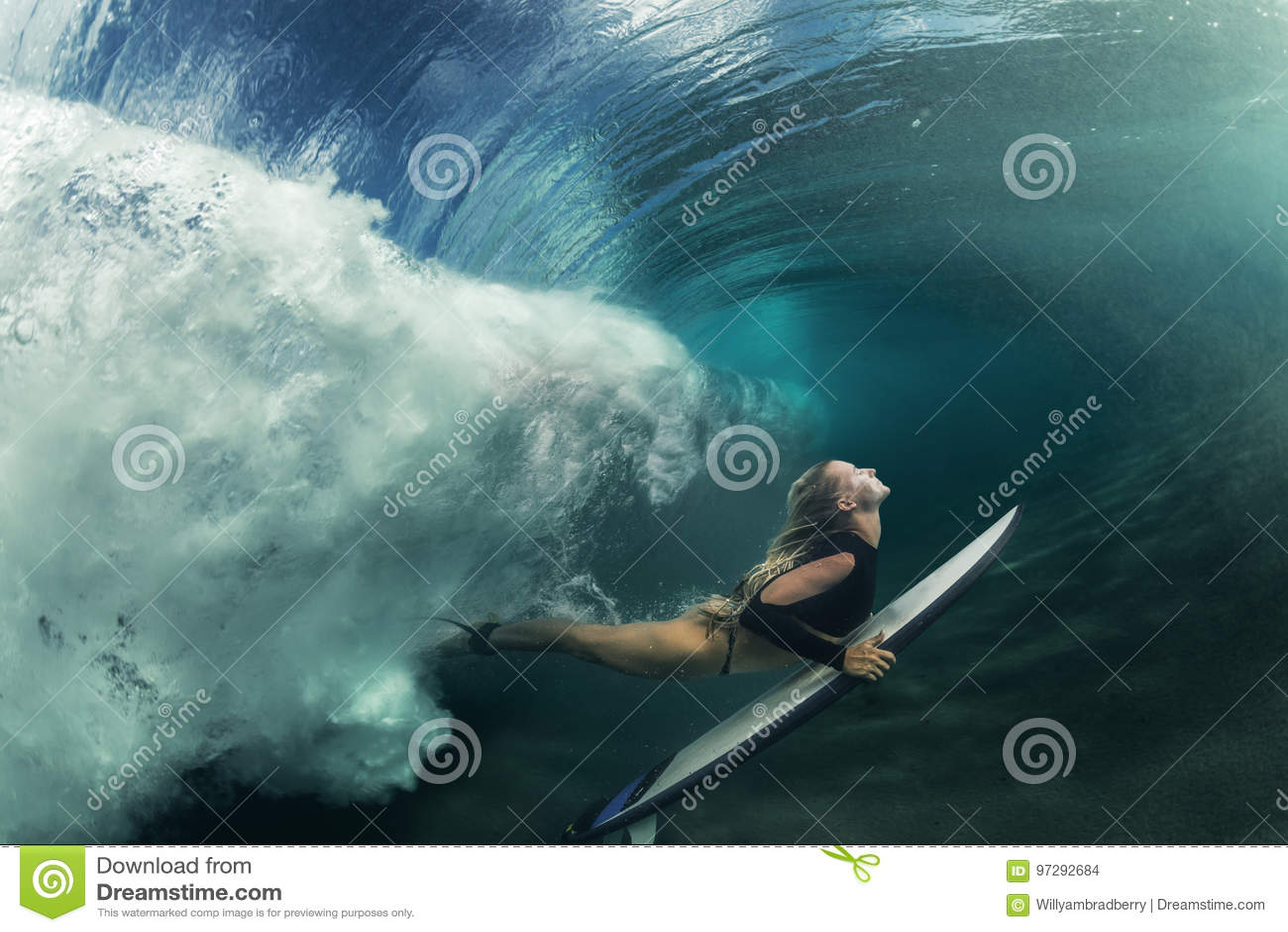 Menina surfando que tem o divertimento sob a onda