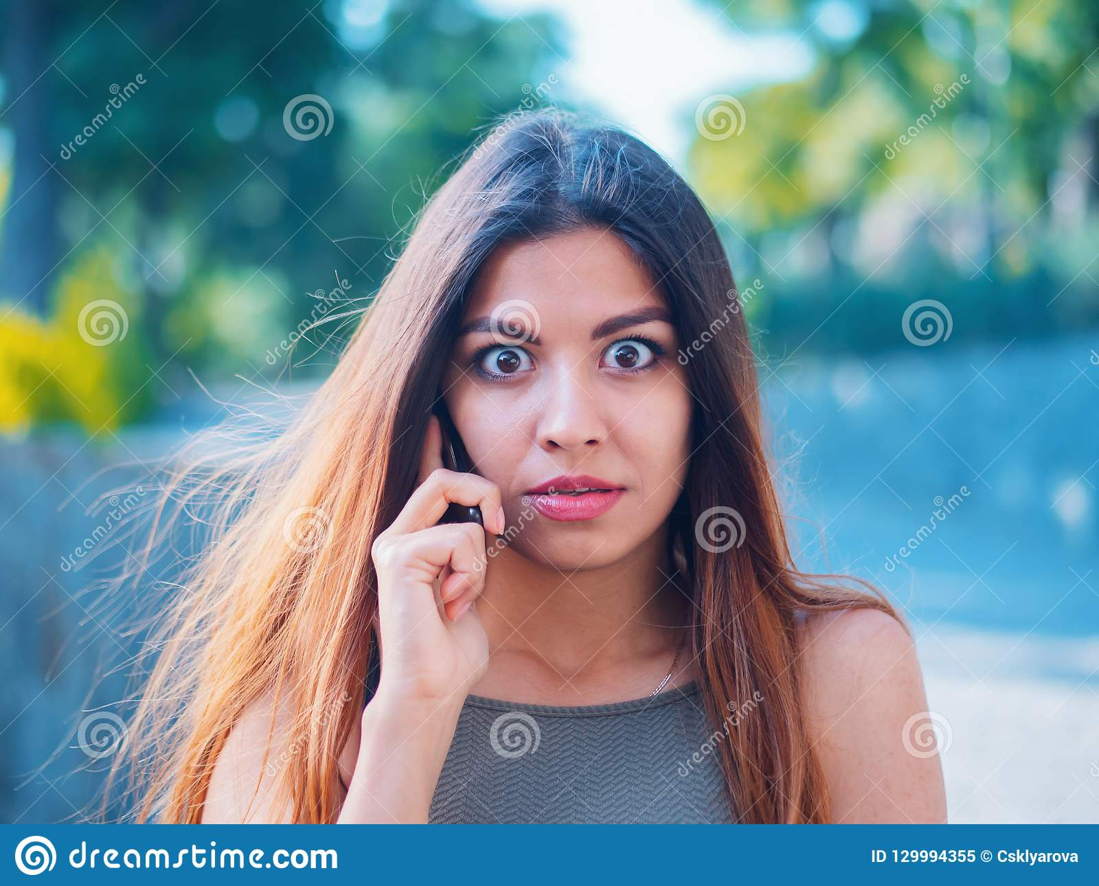 A menina surpreendida ouviu a notícia impressionante no telefone Bisbolhetice com amiga A mulher fala no smartphone Mulher de neg