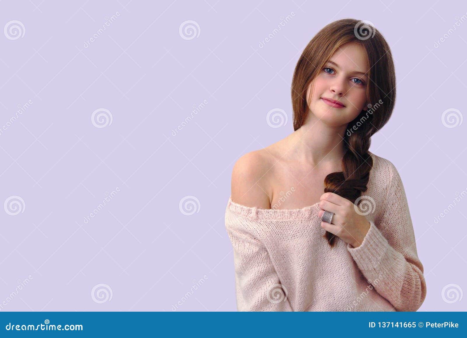 Menina tímida moreno que guarda uma trança em sua mão em um fundo cor-de-rosa