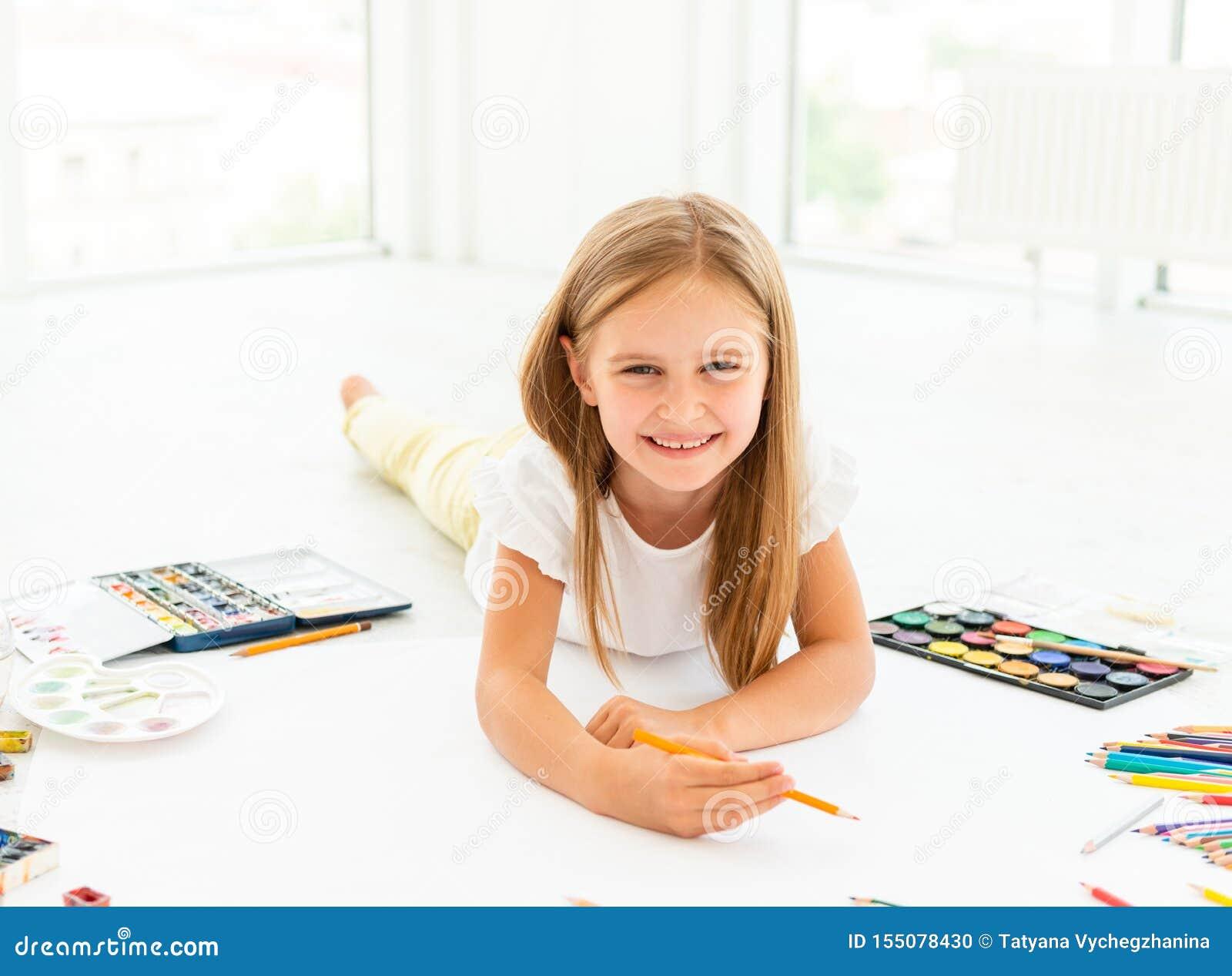 A menina tira o encontro no floorlittle que a menina alegre tira o encontro no assoalho