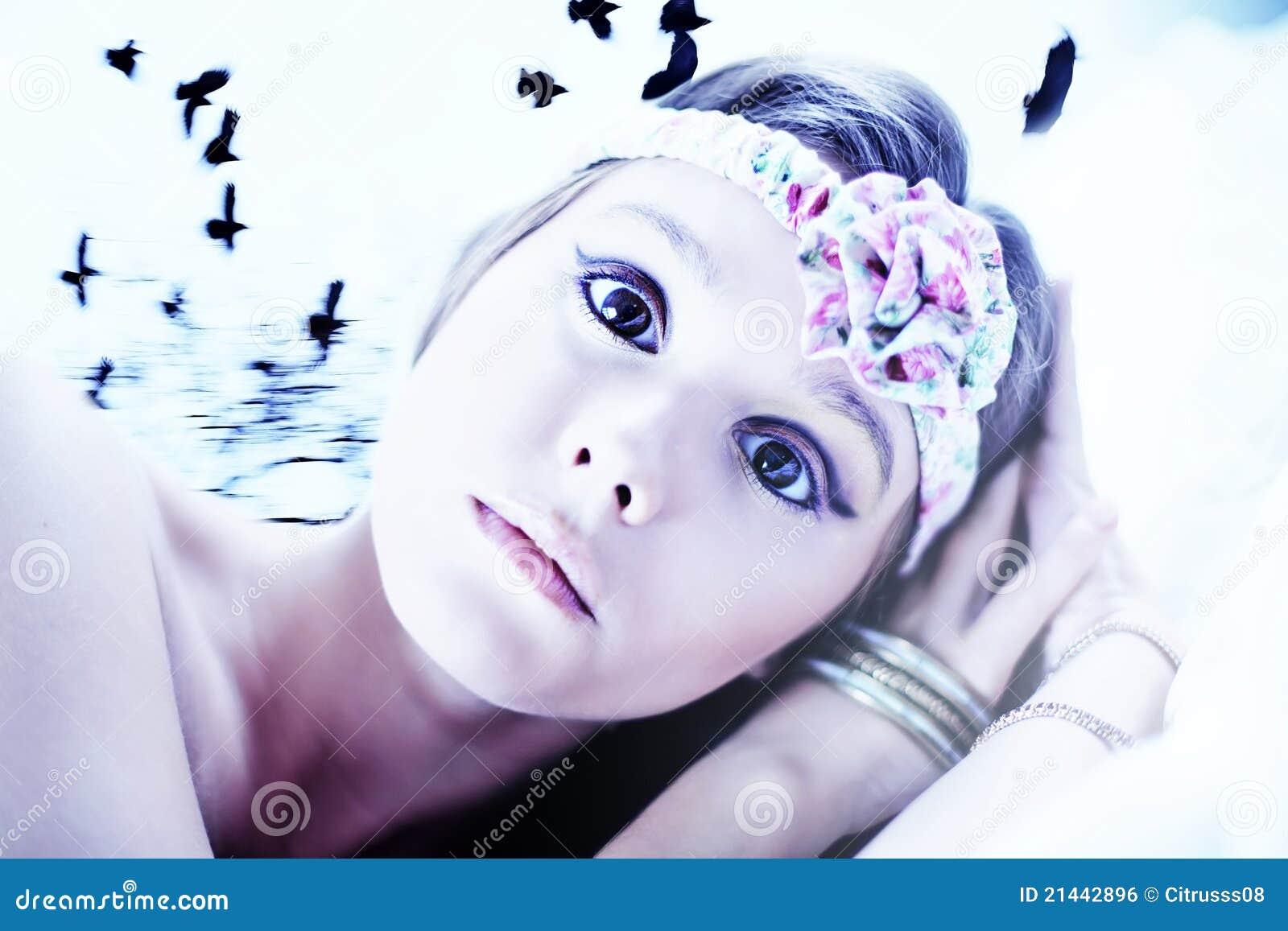 Menina triguenha Scared na cama com corvos