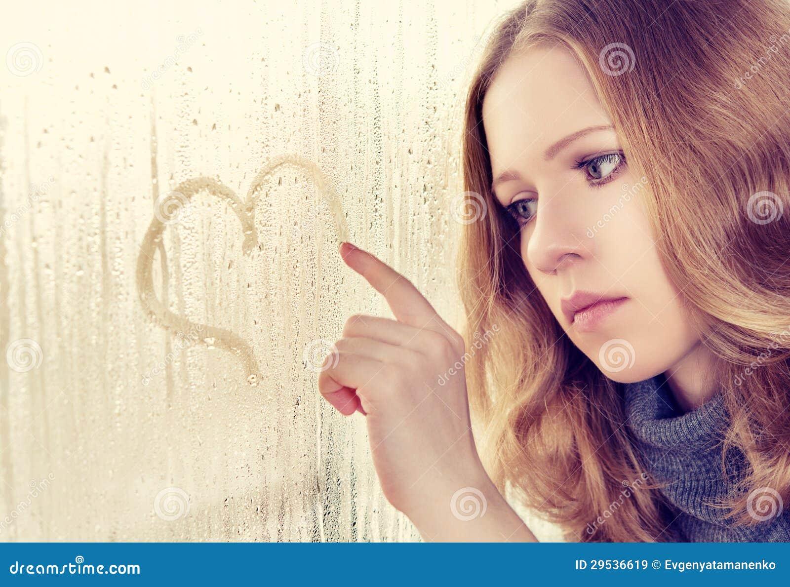 A menina triste desenha um coração no indicador na chuva