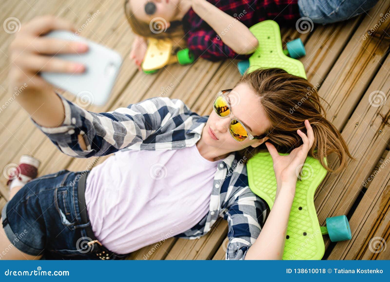 Menina urbana à moda nova no equipamento do moderno que faz o selfie ao encontrar-se com no cais de madeira