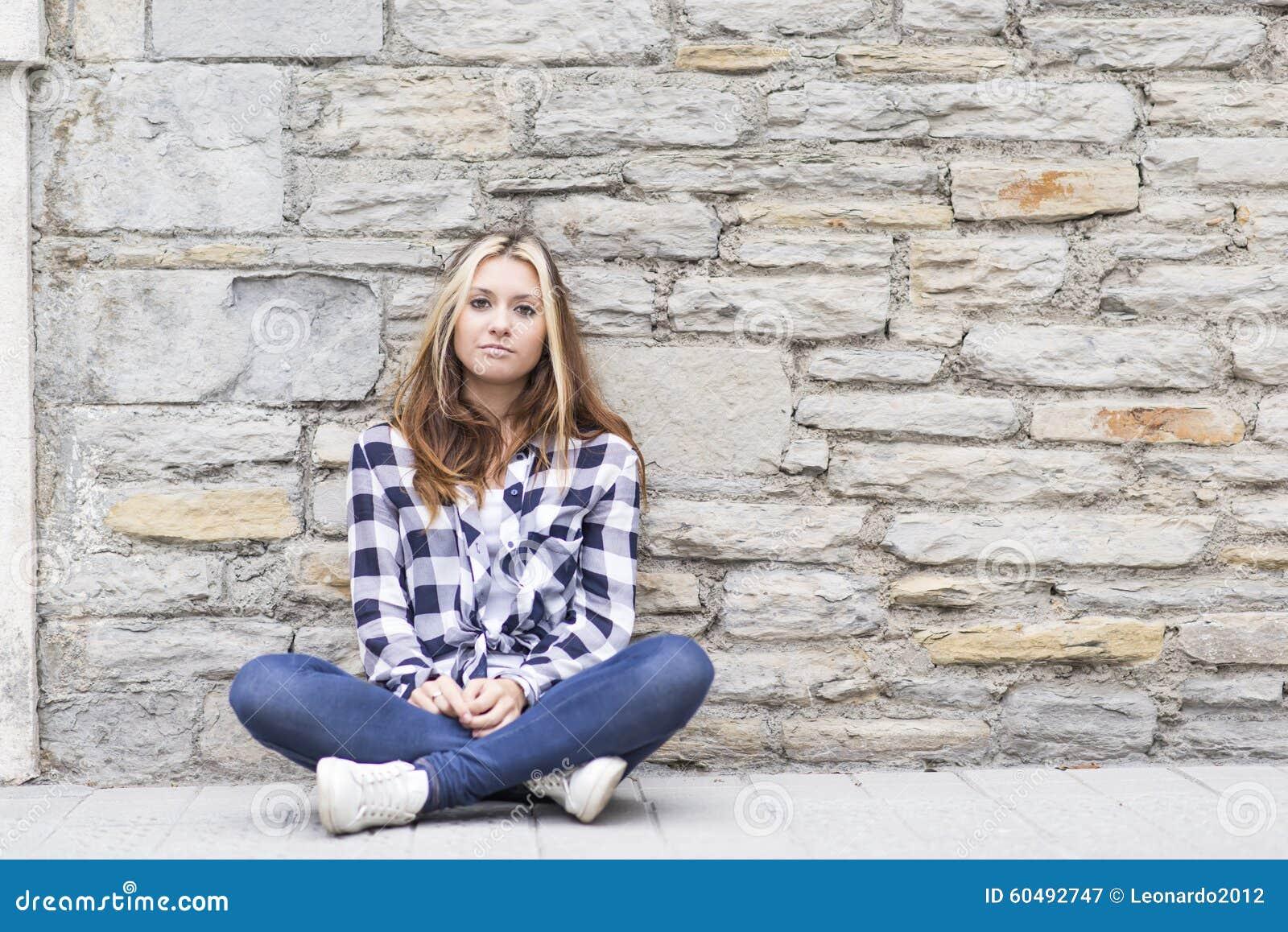 Menina urbana que senta-se na rua e que olha a câmera