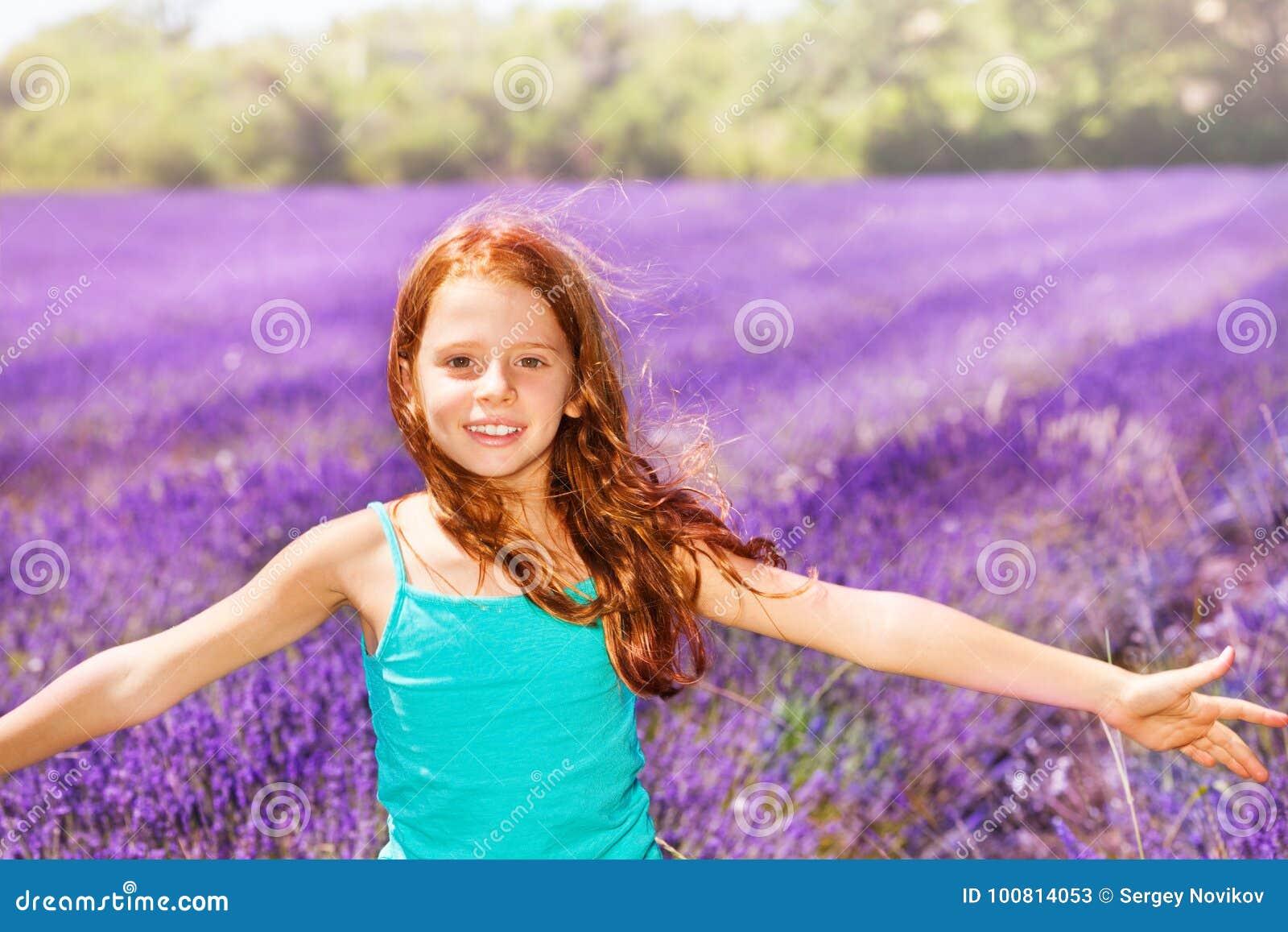 Menina vermelho-dirigida feliz que tem o divertimento no campo da alfazema