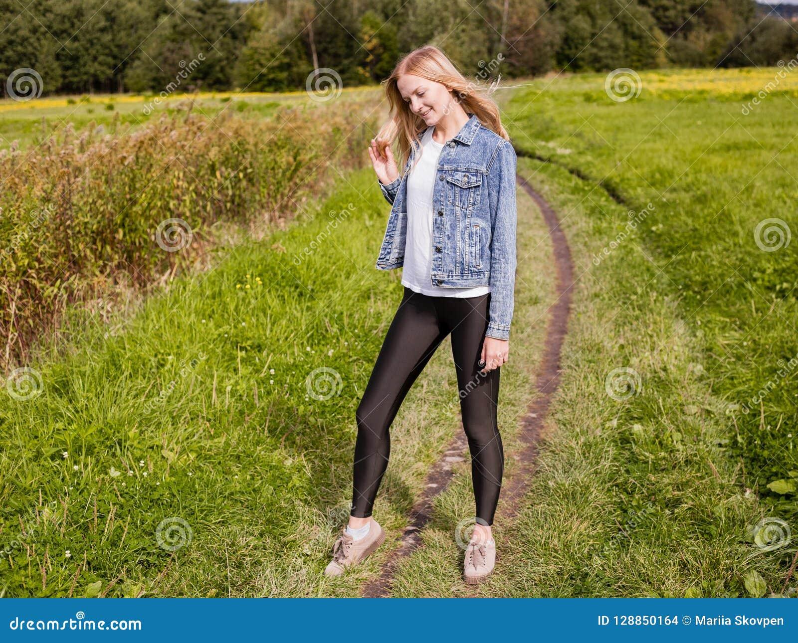 A menina vestiu-se nas caneleiras e no revestimento da sarja de Nimes que anda na estrada secundária