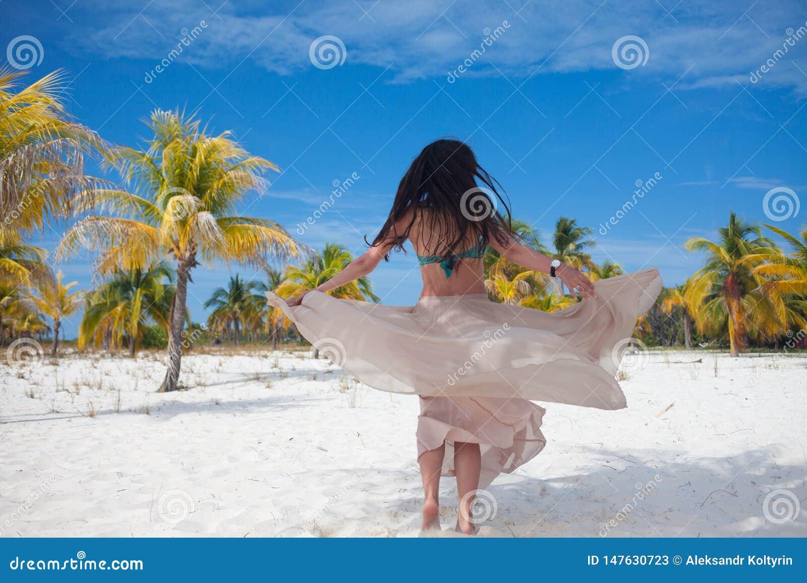 A menina viaja ao mar e está feliz Dança moreno atrativa nova da mulher que acena sua saia contra a paisagem tropical