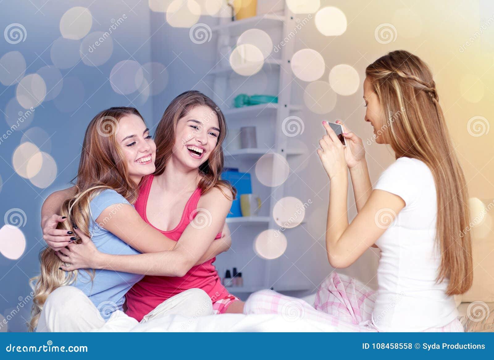 Meninas adolescentes com o smartphone que toma a imagem em casa