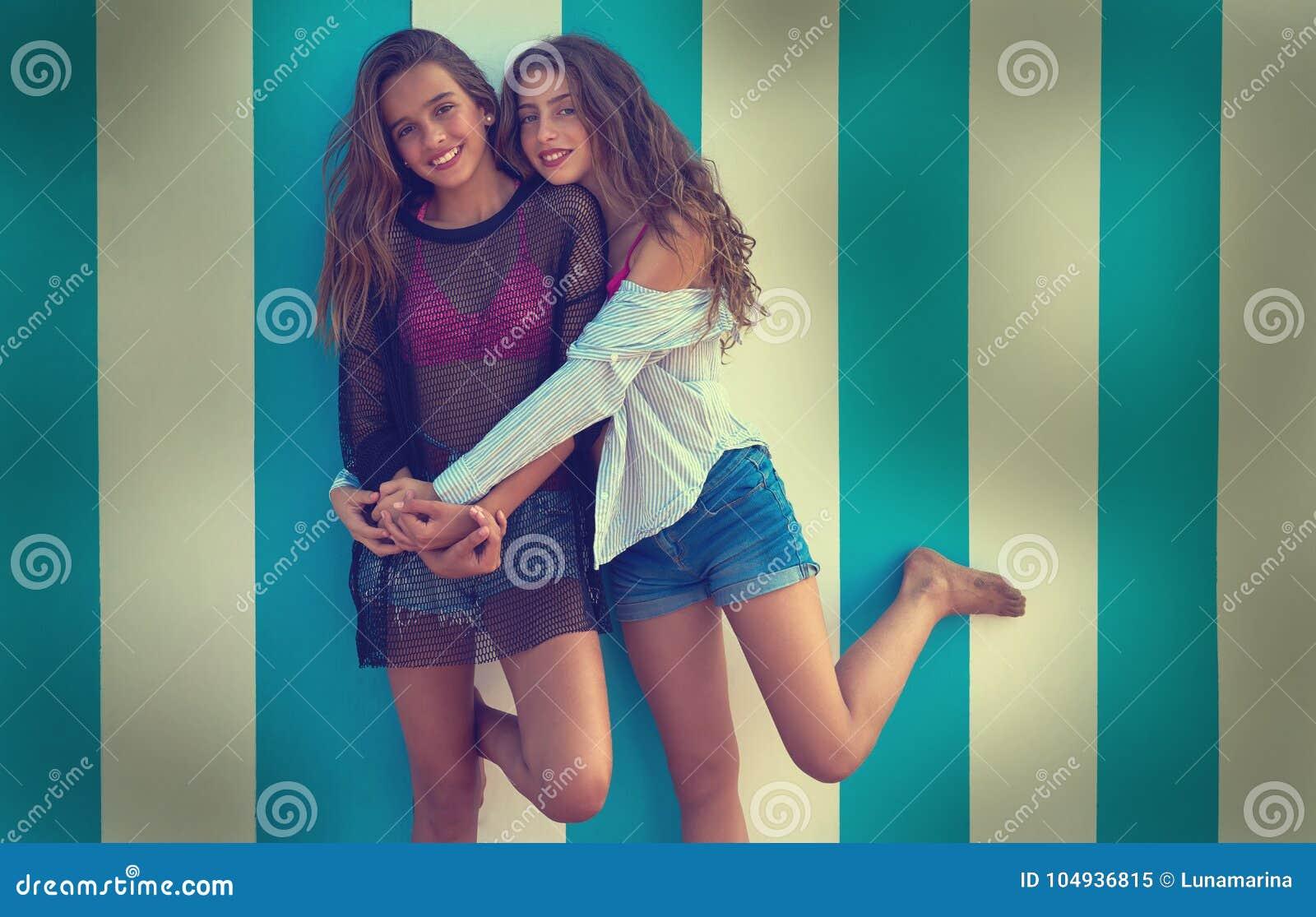 Meninas adolescentes dos melhores amigos felizes na praia do verão