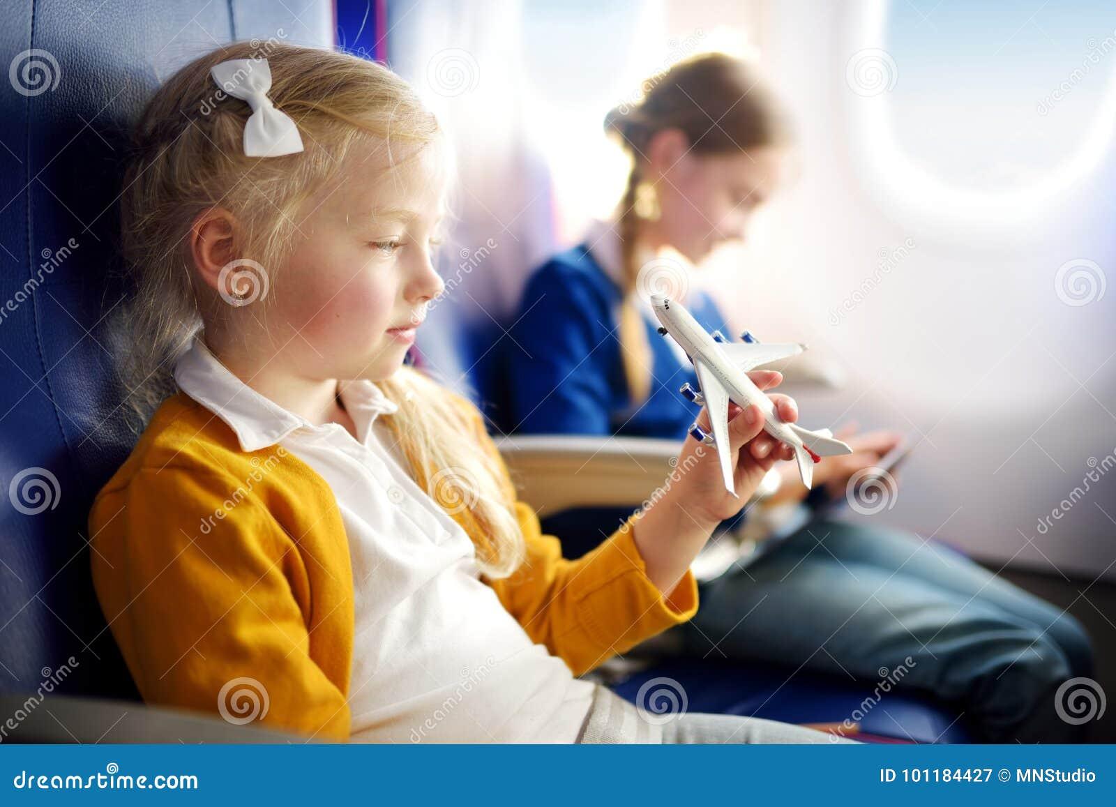 Meninas adoráveis que viajam por um avião Crianças que sentam-se pela janela dos aviões e que jogam com plano do brinquedo Viagem